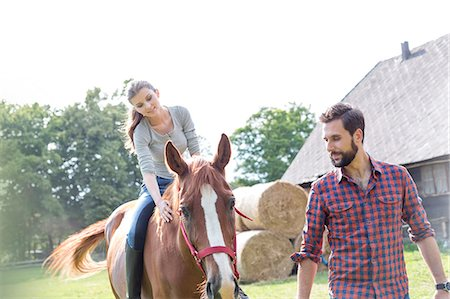 Man leading woman horseback riding in rural pasture Stock Photo - Premium Royalty-Free, Code: 6113-08220413