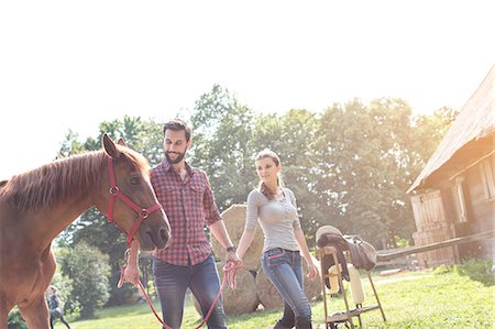 Couple walking horse outside rural barn Stock Photo - Premium Royalty-Free, Code: 6113-08220417