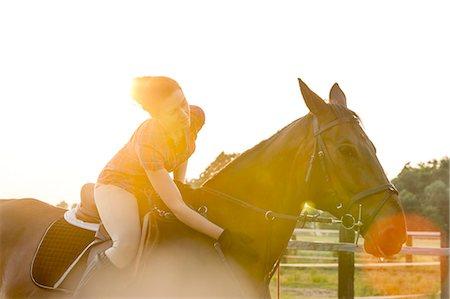 Woman on horseback petting horse in rural pasture Stock Photo - Premium Royalty-Free, Code: 6113-08220424