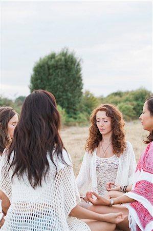Boho women meditating in circle in rural field Stock Photo - Premium Royalty-Free, Code: 6113-08220545