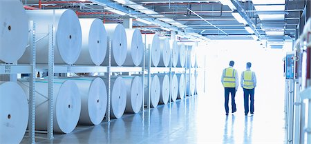 production - Workers in reflective clothing walking along large paper spools in printing plant Stock Photo - Premium Royalty-Free, Code: 6113-08393662