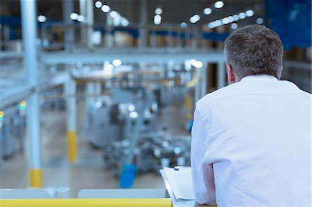 supervising - Supervisor with clipboard on platform overlooking factory Stock Photo - Premium Royalty-Free, Code: 6113-08393670