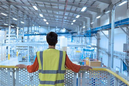 supervising - Worker in reflective clothing on platform looking out over factory Stock Photo - Premium Royalty-Free, Code: 6113-08393676