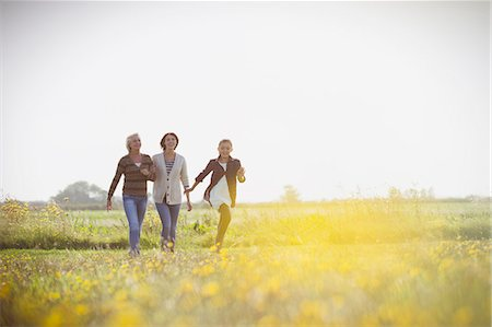 Multi-generation women walking in sunny meadow Stock Photo - Premium Royalty-Free, Code: 6113-08393683
