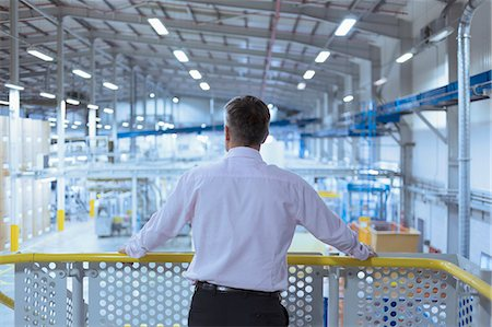 supervising - Supervisor on platform looking out over factory Stock Photo - Premium Royalty-Free, Code: 6113-08393601