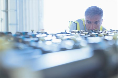 equipment - Engineer examining printing press conveyor belt Stock Photo - Premium Royalty-Free, Code: 6113-08393637