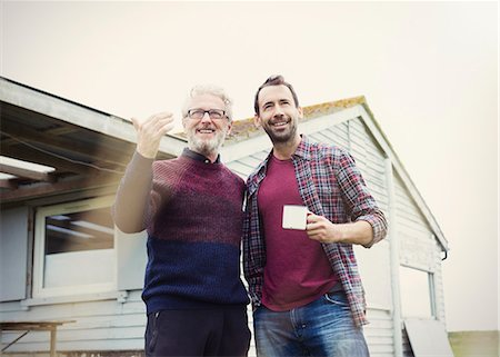 Father and son talking and drinking coffee outside house Stock Photo - Premium Royalty-Free, Code: 6113-08393741