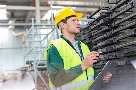 piles of work - Worker in protective workwear with clipboard examining steel parts in factory Stock Photo - Premium Royalty-Free, Code: 6113-08393850