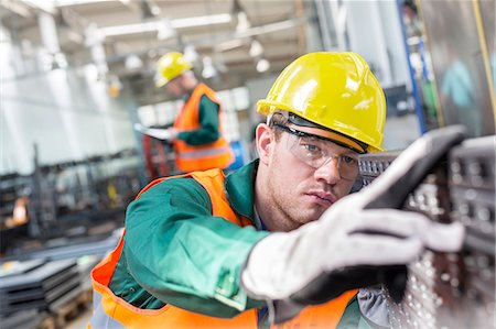 Focused worker examining steel part in factory Stock Photo - Premium Royalty-Free, Code: 6113-08393857