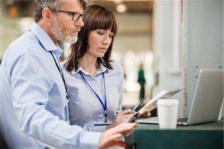 production - Business people with clipboard working at laptop in factory Stock Photo - Premium Royalty-Free, Code: 6113-08393888