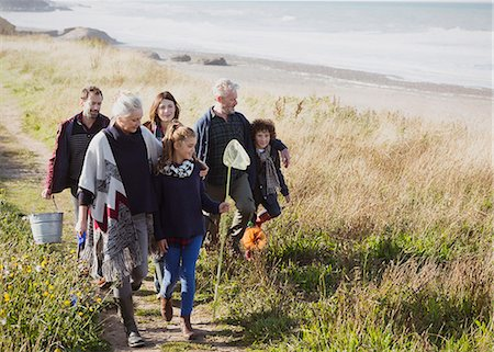 Multi-generation family walking with nets and bucket on sunny grass beach path Stock Photo - Premium Royalty-Free, Code: 6113-08393810