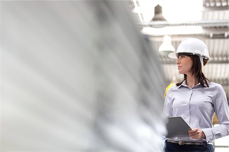 supervising - Businesswoman in hard-hat and clipboard working in factory Stock Photo - Premium Royalty-Free, Code: 6113-08393824