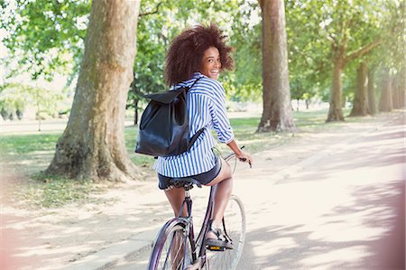 Portrait smiling woman with afro riding bicycle in park Foto de stock - Sin royalties Premium, Código: 6113-08321095