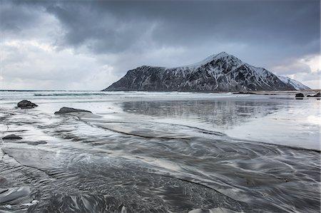 Snow covered rock formation on cold ocean beach, Skagsanden Beach, Lofoten Islands, Norway Stock Photo - Premium Royalty-Free, Code: 6113-08321251
