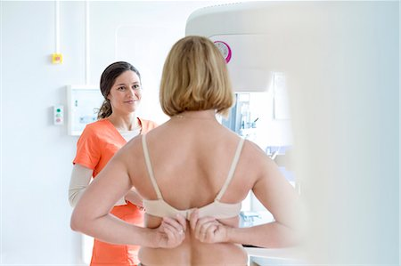 Nurse helping patient prepare for mammogram in examination room Stock Photo - Premium Royalty-Free, Code: 6113-08321284