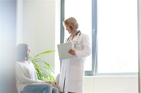 doctor in waiting room - Doctor with medical record talking to patient in waiting room Stock Photo - Premium Royalty-Free, Code: 6113-08321288