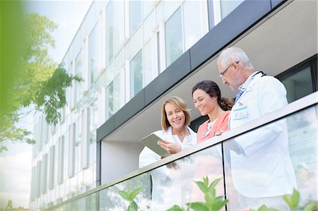 simsearch:6113-07146726,k - Doctors and nurse reviewing medical record on hospital balcony Stock Photo - Premium Royalty-Free, Code: 6113-08321301