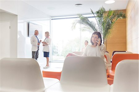 Woman talking on cell phone in hospital lobby Stock Photo - Premium Royalty-Free, Code: 6113-08321305
