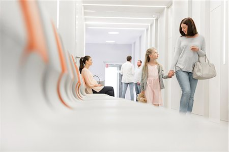 Mother and daughter holding hands walking in hospital corridor Stock Photo - Premium Royalty-Free, Code: 6113-08321336