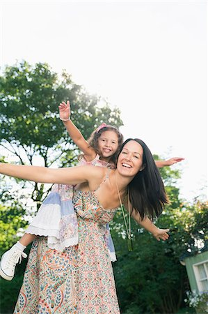 Portrait carefree mother piggybacking daughter with arms outstretched Stock Photo - Premium Royalty-Free, Code: 6113-08321580