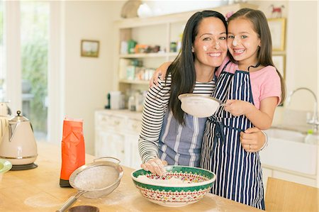 Portrait playful mother and daughter baking in kitchen with flour on faces Stock Photo - Premium Royalty-Free, Code: 6113-08321581