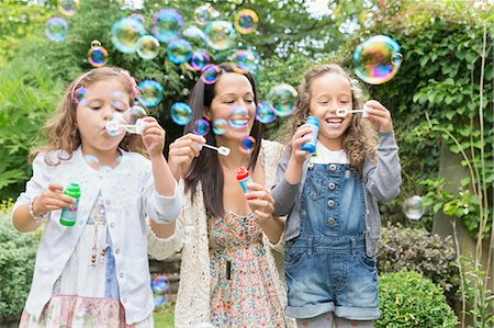 Mother and daughters blowing bubbles in backyard Stock Photo - Premium Royalty-Free, Code: 6113-08321644