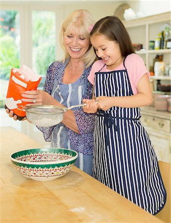 Grandmother and granddaughter baking sifting flour in kitchen Stock Photo - Premium Royalty-Free, Code: 6113-08321653