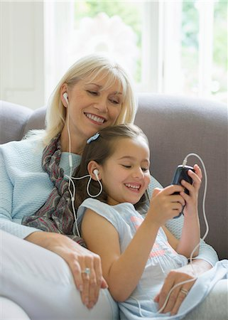 Grandmother and granddaughter sharing headphones listening to music on sofa Stock Photo - Premium Royalty-Free, Code: 6113-08321654