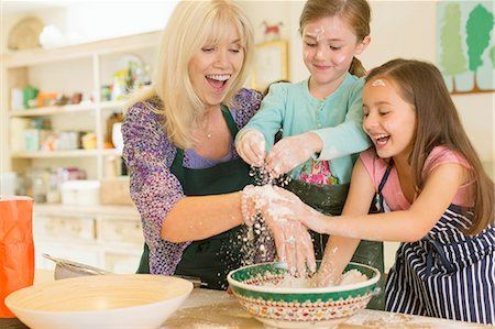 Playful grandmother and granddaughters sprinkling flour in kitchen Stock Photo - Premium Royalty-Free, Code: 6113-08321655