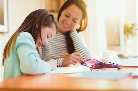Mother watching daughter do homework Stock Photo - Premium Royalty-Free, Code: 6113-08321613