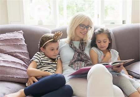 Grandmother and granddaughters reading book on living room sofa Stock Photo - Premium Royalty-Free, Code: 6113-08321624