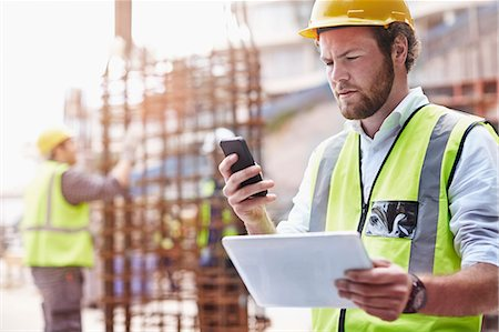 Construction worker with digital tablet texting with cell phone at construction site Stock Photo - Premium Royalty-Free, Code: 6113-08321744