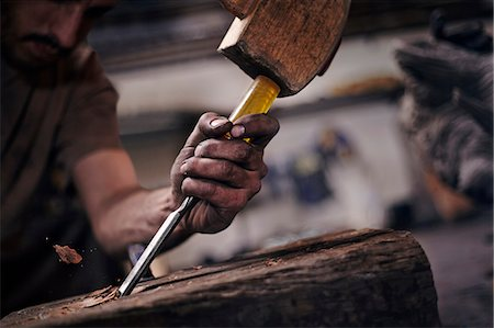 dirty - Close up of blacksmith chiseling wood with tool Stock Photo - Premium Royalty-Free, Code: 6113-08424276