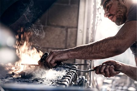 Blacksmith working over fire in forge Stock Photo - Premium Royalty-Free, Code: 6113-08424282
