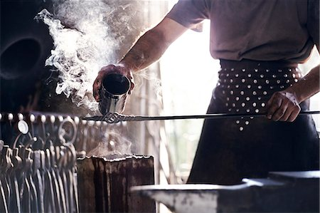 Blacksmith pouring hot liquid over wrought iron in forge Stock Photo - Premium Royalty-Free, Code: 6113-08424300
