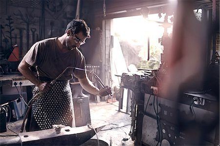 Blacksmith using blow torch in forge Stock Photo - Premium Royalty-Free, Code: 6113-08424305