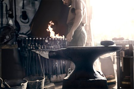 Blacksmith at fire behind anvil in forge Stock Photo - Premium Royalty-Free, Code: 6113-08424316