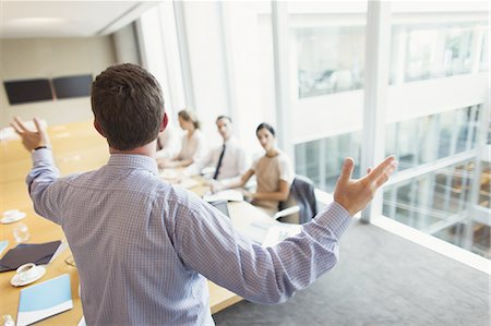 Businessman gesturing to colleagues in conference room meeting Stock Photo - Premium Royalty-Free, Code: 6113-08549970