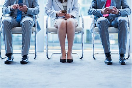 Business people with cell phones waiting in a row Stock Photo - Premium Royalty-Free, Code: 6113-08549977
