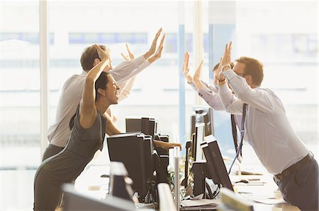 Exuberant business people high-fiving over computers in office Stock Photo - Premium Royalty-Free, Code: 6113-08549934