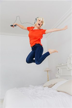 Playful woman jumping on bed listening to music with headphones and mp3 player Stock Photo - Premium Royalty-Free, Code: 6113-08550044