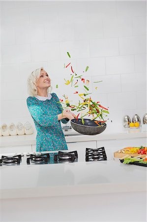 Woman cooking flipping vegetables in skillet in kitchen Stock Photo - Premium Royalty-Free, Code: 6113-08550064