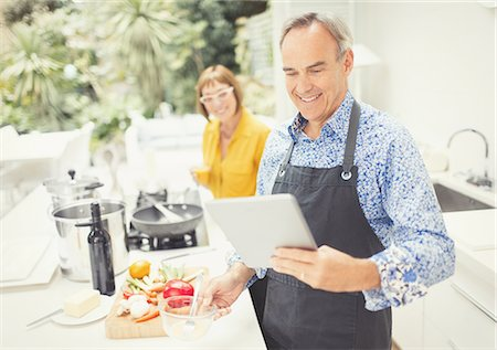 Mature couple with digital tablet cooking in kitchen Stock Photo - Premium Royalty-Free, Code: 6113-08550090