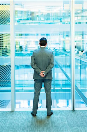 Businessman standing at atrium window with hands behind back Stock Photo - Premium Royalty-Free, Code: 6113-08550013