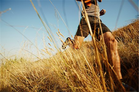 exercising - Man running through tall grass on sunny trail Stock Photo - Premium Royalty-Free, Code: 6113-08550157