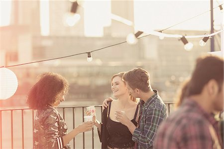 party - Young adult friends talking and drinking at rooftop party Stock Photo - Premium Royalty-Free, Code: 6113-08568565