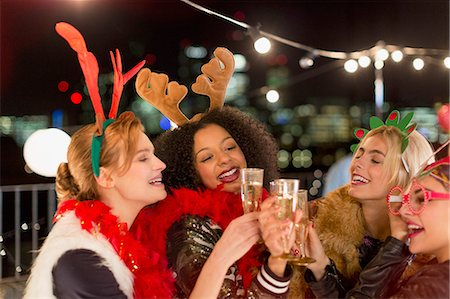 Young women wearing Christmas reindeer antlers and toasting champagne glasses at rooftop party Stock Photo - Premium Royalty-Free, Code: 6113-08568502