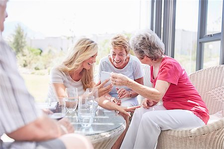 Senior women using cell phone on patio Stock Photo - Premium Royalty-Free, Code: 6113-08568750