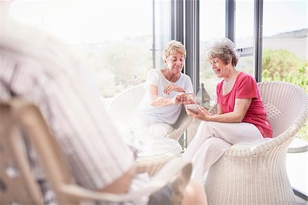 senior women - Senior women using cell phone on patio Stock Photo - Premium Royalty-Free, Code: 6113-08568771