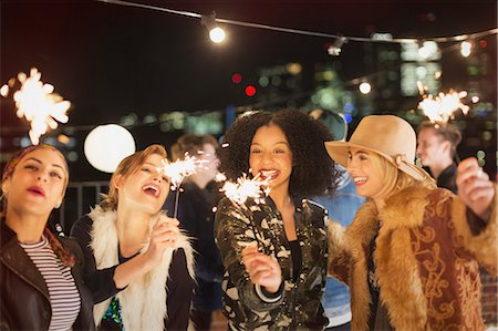 Young women with sparklers at rooftop party Stock Photo - Premium Royalty-Free, Code: 6113-08568783